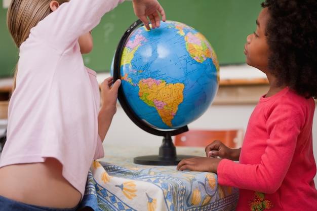 Cute little schoolgirls looking at a globe