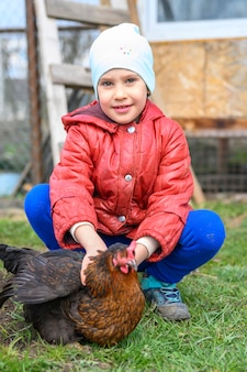 Cute little seven year old kid girl holding in hands a brown chicken in nature outdoor