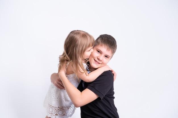 Милая маленькая сестра целует, обнимая своего красивого старшего брата-подростка на белом фоне.