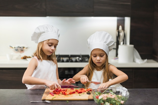 Cute little sisters cutting bell pepper on cutting board while preparing food