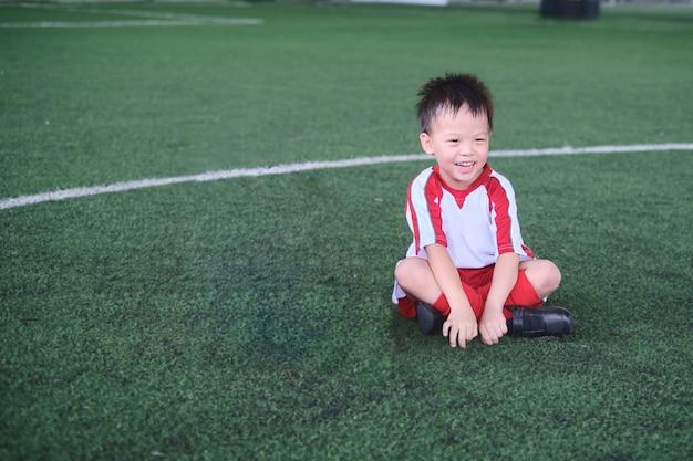 웃고 있는 귀여운 아시아 4세 유치원 아이, 축구 유니폼을 입은 축구 선수가 훈련 세션, 어린이를 위한 축구 훈련, 선택적 집중에서 축구를 하고 있습니다.