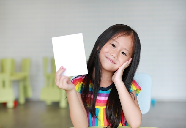 Cute little smiling asian child girl holding blank white paper card in her hand