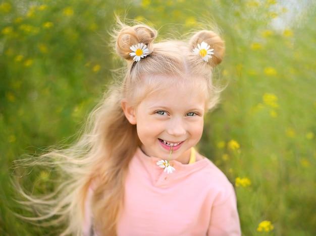 Милая маленькая улыбающаяся блондинка с ромашкой в прическе и в зубах