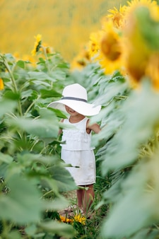 A cute little smiling girl in the field of sunflowers. child in momy hat. childhood concept. sunny summer day in field of sunflowers. selective focus