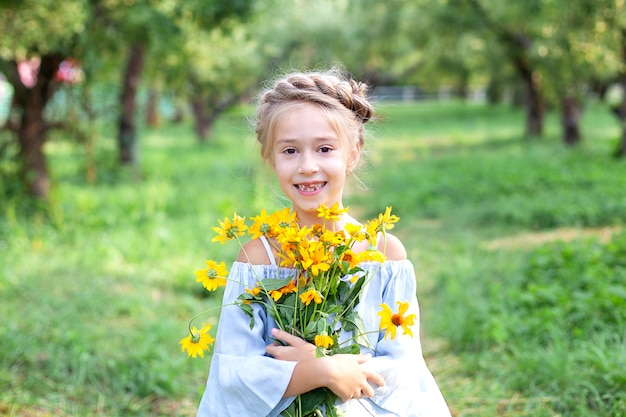 Cute little smiling girl in with a bouquet of yellow flowers in garden. cheerful child with daisies. portrait little girl with bouquet of chamomiles in sunny summer day. gardening. childhood concept.