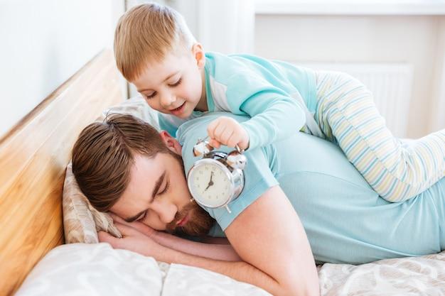 自宅で眠っている父の耳の近くに目覚まし時計を持っているかわいい幼い息子