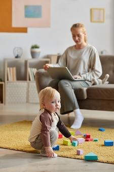 彼の母親がソファに座ってラップトップに取り組んでいる間、床でおもちゃで遊んでいるかわいい幼い息子
