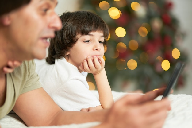 귀여운 작은 아들이 침대에 누워 디지털 태블릿을 사용하여 아버지를 지켜보고 있습니다. 아버지와 아이는 크리스마스를 위해 장식된 집에서 함께 시간을 보내는 동안 화면을 보고 있습니다. 기술, 어린 시절