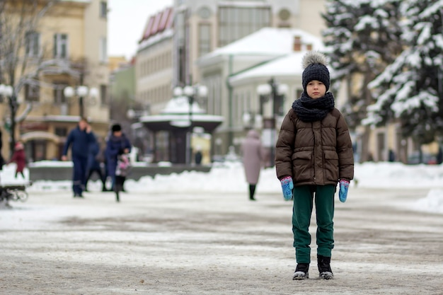Cute little stylish boy in classic style in the city.