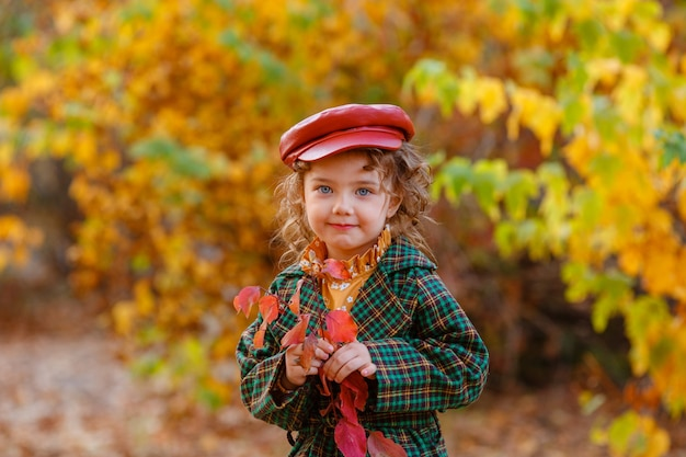 Cute little stylish girl in the autumn park