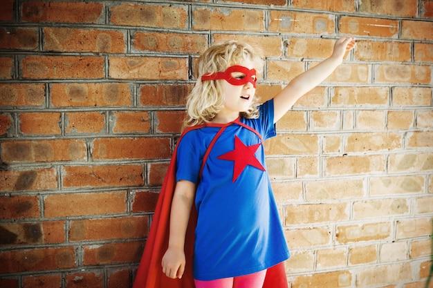 벽돌 벽에 귀여운 슈퍼 영웅 소녀. 슈퍼 히어로 개념.