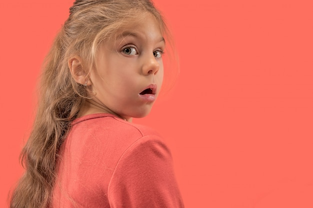 Cute little surprised girl in coral dress with long hair smiling to camera