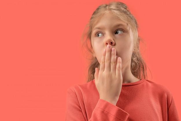 Милая маленькая удивленная девушка в коралловом платье с длинными волосами, улыбаясь в камеру