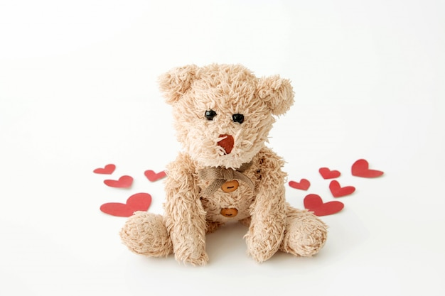 The cute little teddy bear is so happy with many hearts in valentine.