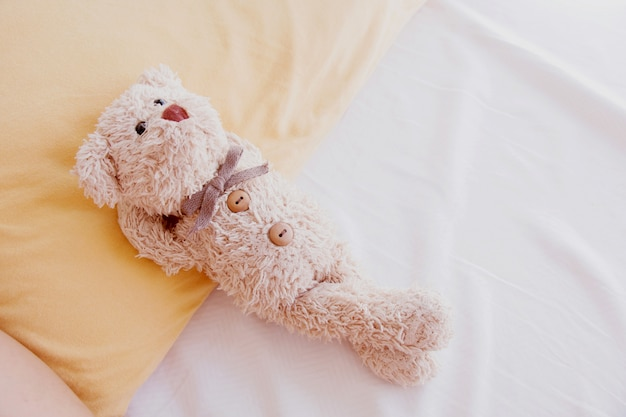 Cute little teddy bear lay down on the bed.