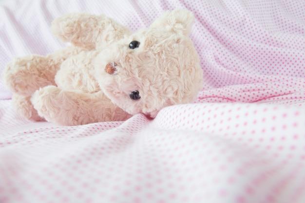 Cute little teddy bear lay down on the bed