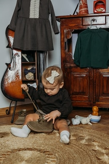 Cute little toddler baby girl in vintage clothes playing at home genderneutral baby fashion unisex