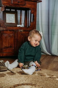 Cute little toddler baby girl in vintage clothes playing with beads at home genderneutral baby