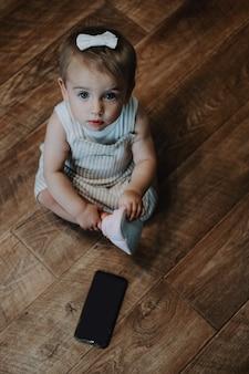 床の近くに座っている子供の縦の肖像画の近くに携帯電話を持つかわいい幼児の女の赤ちゃん