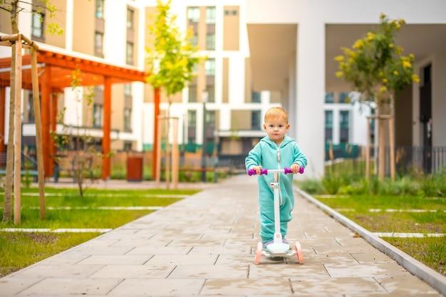 Милая маленькая девочка в синем комбинезоне катается на самокате, счастливая, здоровая, прекрасная ...