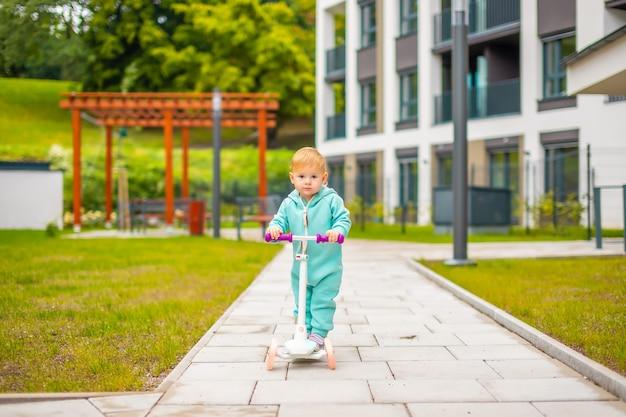 Милая маленькая девочка-малышка в синем комбинезоне катается на самокате счастливая здоровая прекрасная малышка ... Premium Фотографии