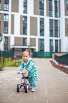 ランバランスバイクに乗っている青いオーバーオールのかわいい幼児の女の子幸せで健康的な素敵な赤ちゃん...