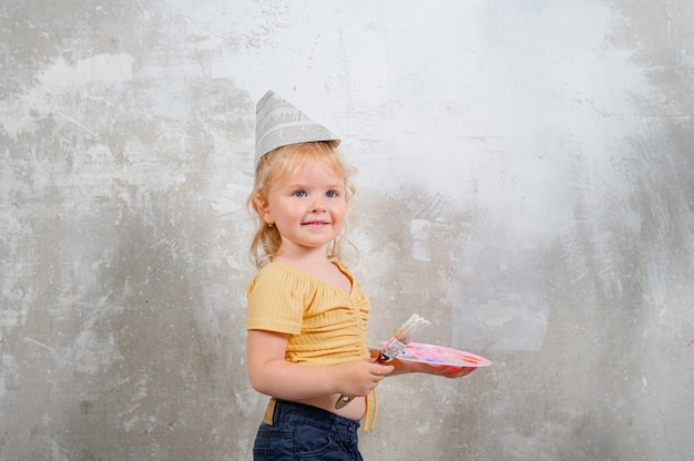 Cute little toddler girl is painting a wall in a new home family home renovation
