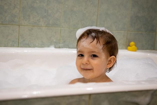 귀여운 어린 소녀가 비누 거품으로 목욕을 하고 머리를 닫고 웃는다