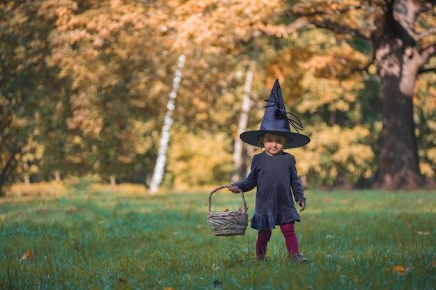 秋の森のハロウィーンの衣装でかわいい幼児のgiirl魔女