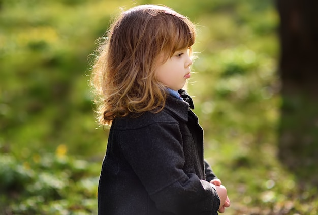 Cute little unhappy girl outdoors portrait in spring sunny day