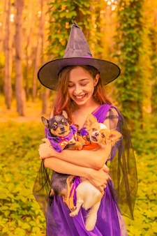 Cute little witch with dogs. beautiful young child girl in witch costume outdoors. halloween.
