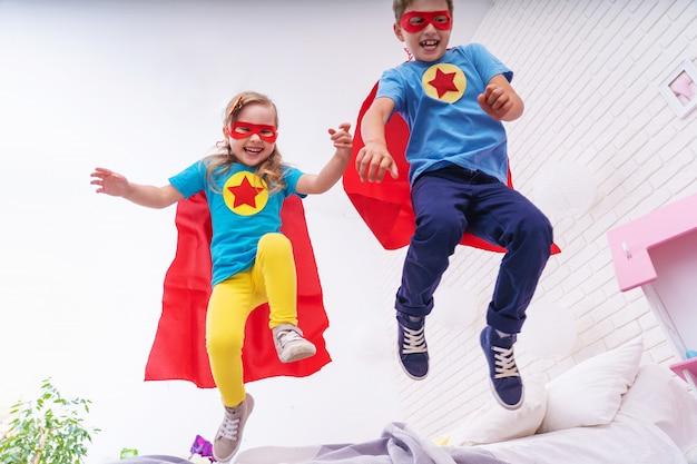 Милая маленькая женщина и мальчик прыгает с кровати, чтобы летать