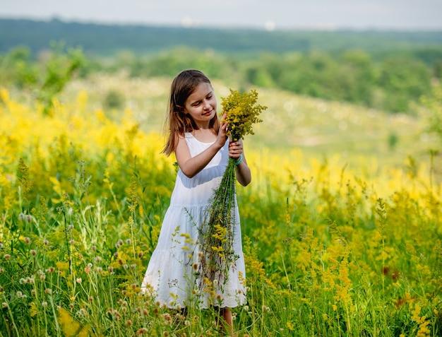 咲くフィールドの背景に野花の花束を保持しているかわいい女性
