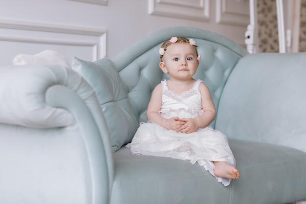 白いドレスと頭の上の花のフープでかわいい小さな女性は、クラシックなスタイルのソファに座って、家で楽しんでいます。