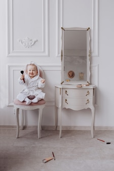 A cute little woman is holding a makeup brush and having fun at home. baby girl is sitting on the chair near the classic mirror indoors . kid's fashion. little girl fashionista.
