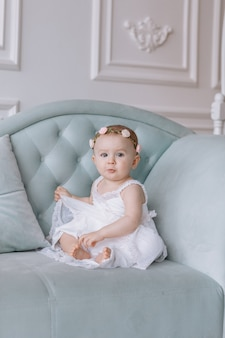 Cute little woman in white dress and hoops of flowers on head is sitting on a couch in a classic style and having fun at home.