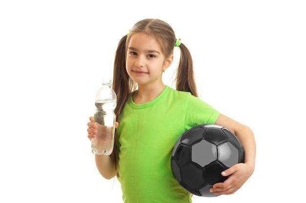 Милая маленькая женщина с футбольным мячом в руках пьет воду в бутылке, изолированной на белом
