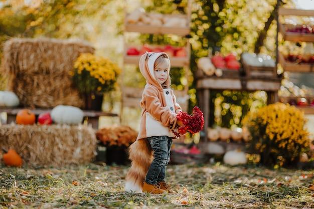 屋外市場で赤い灰の果実の束でポーズをとって尾を持つ赤いキツネのコートでかわいい女の子。