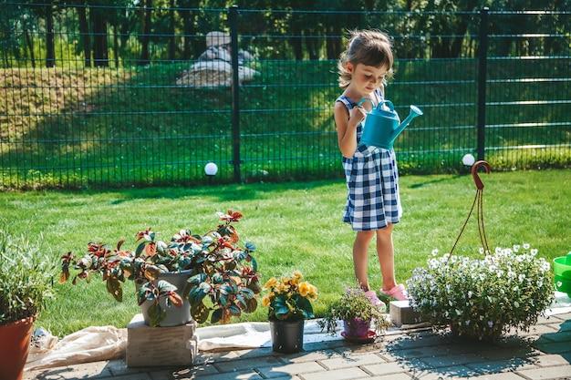 정원에 있는 물뿌리개에서 식물에 물을 주는 파란색 격자 무늬 드레스를 입은 3-4세의 귀여운 소녀입니다. 밖에서 즐겁게 노는 아이들. 야외 활동 어린이.