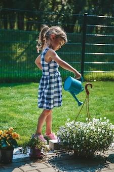 정원에 있는 물뿌리개에서 식물에 물을 주는 파란색 격자 무늬 드레스를 입은 3-4세의 귀여운 소녀입니다. 야외 활동 어린이.