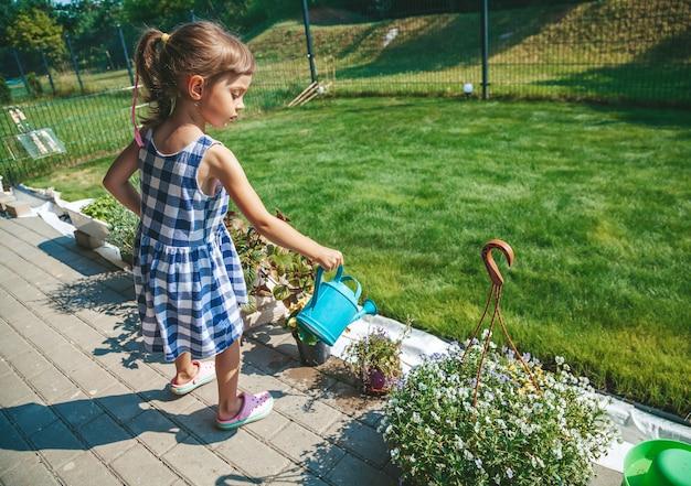 Милая маленькая девочка 3-4 лет в синем клетчатом платье поливает растения из лейки в саду
