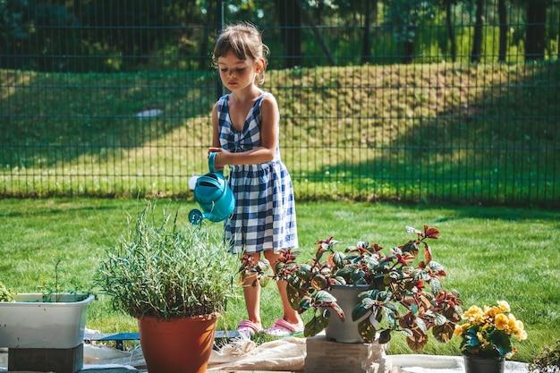 정원에 있는 물뿌리개에서 식물에 물을 주는 파란색 격자 무늬 드레스를 입은 3-4세의 귀여운 소녀