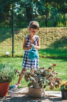 Милая маленькая девочка 3-4 лет в синем клетчатом платье поливает растения из лейки во дворе