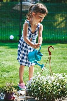 정원에 있는 물뿌리개에서 식물에 물을 주는 파란색 격자 무늬 드레스를 입은 귀여운 소녀