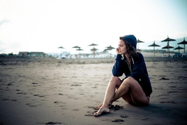 Милая одинокая кавказская молодая девушка сидит на пляже на песке, смотрит на открытое пространство и думает
