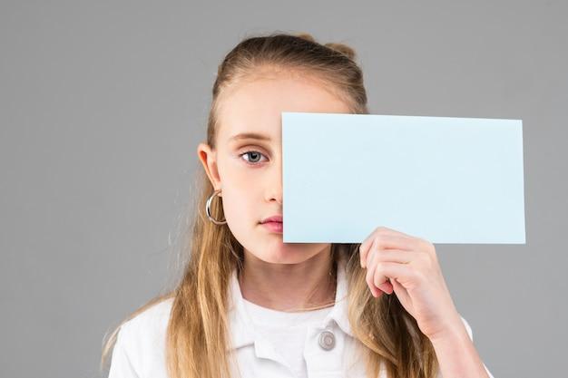 Милая длинноволосая маленькая леди с голубыми глазами держит пустую бумагу и закрывает половину ее лица