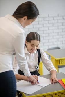 귀여운 긴 머리 웃는 여학생은 그녀의 책상과 교사가 수업 시간에 그녀를 돕는 글을 쓰고 있습니다.