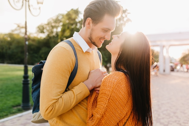 Cute long-haired woman in knitted orange sweater looking into boyfriend's eyes with love in sunny autumn day