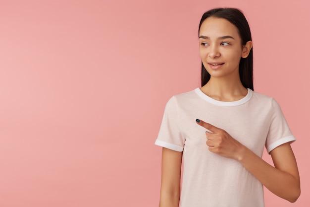 Симпатичная женщина, красивая девушка с длинными черными волосами. в белой футболке. концепция людей. наблюдая и указывая указательным пальцем влево на место для копирования, изолированное на пастельно-розовой стене