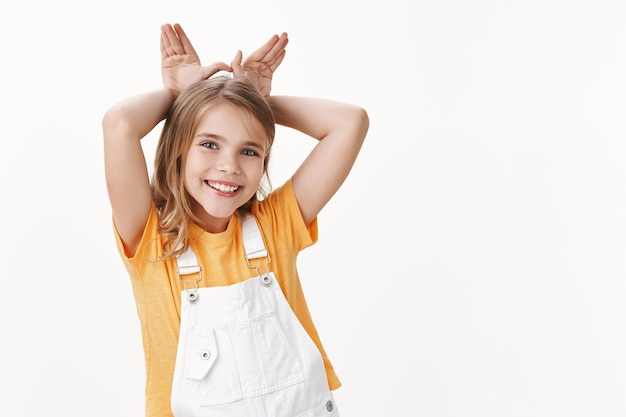 Cute lovely charming little girl, blond child in t-shirt, overalls, show bunny ears mimicking rabit, hold palms behind head, smiling joyfully, playing acting sweet and tender, white wall